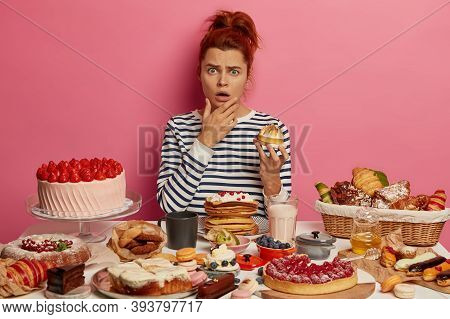 Indignant Red Haired Woman In Striped Jumper Shocked How Much Calories She Ate For Day, Holds Sweet