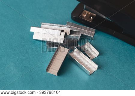 A Set Of Office Supplies. Stapler And Staples On Blue Background.