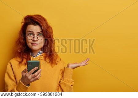 Indignant Puzzled Redhead Woman Raises Palm, Thinks What To Answer On Received Message, Holds Mobile