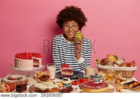 Unhealthy Food And Diet Fail Concept. Glad Curly Young Afro American Woman Takes High Calories Crois
