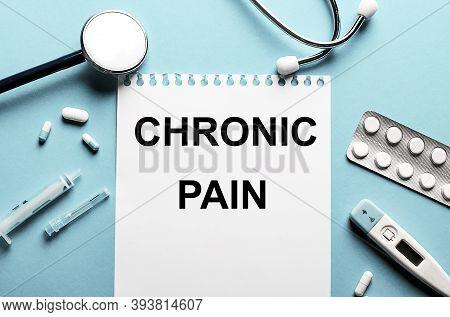 Chronic Pain Written On A White Notepad On A Blue Background Near A Stethoscope, Syringe, Electronic