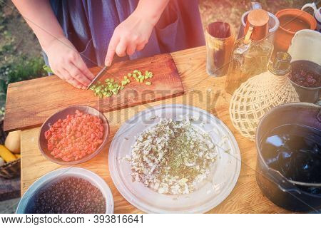 Life Of The First Pioneers Of America. The Girl Prepares Food In The Kitchen For The First Settlers