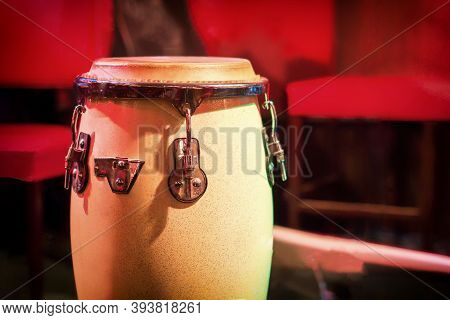 Traditional Ethnic Cuban Djembe Drum On Red Background. Percussion Instruments Made Of Wood Covered