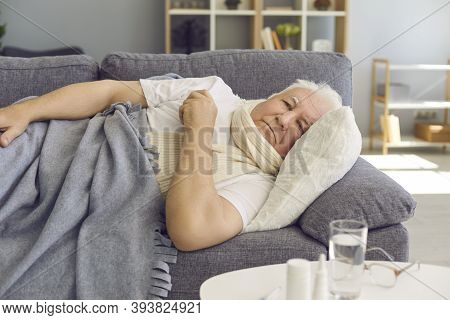 Unhappy Senior Man Lying On Sofa At Home, Suffering From Bad Cold, Flu Or Covid Fever