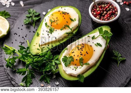Homemade Organic Egg Baked In Avocado With Salt And Pepper. Avocado Stuffed With Eggs. Delicious Bre