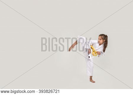 Full Length Shot Of Little Karate Girl In White Kimono With A Yellow Sash Exercising And Fighting, D