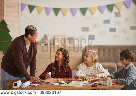 Multi-ethnic Group Of Children Drawing Pictures Together While Enjoying Art And Craft Class With Smi