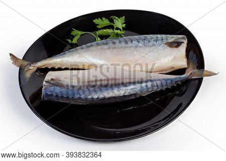 Two Salted Gutted Headless Atlantic Mackerel And Twig Of Parsley On The Black Dish On A White Backgr