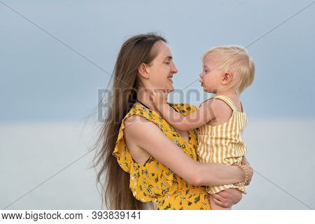 Portrait Of Beautiful Young Mother Hugging Her Little Daughter On Sea Background