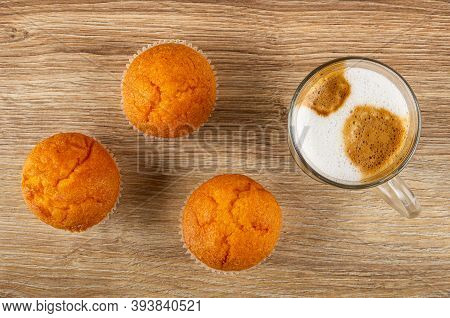 Three Orange Muffins, Transparent Glass Cup With Latte-macchiato On Wooden Table. Top View