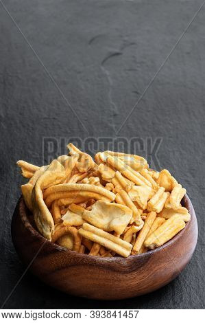 Savoury  Indian Snack In Wooden Bowl On Black Stone Background