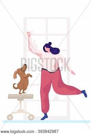 Young Woman Is Training The Animal At Home. The Dog Is Standing On Its Hind Legs. Trainer Holding Bo