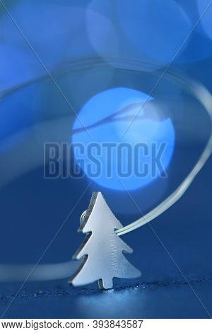 Christmas And New Year Concept. Christmas Tree Shiny Decor On Blue Glitter With A Blue Bokeh Backgro