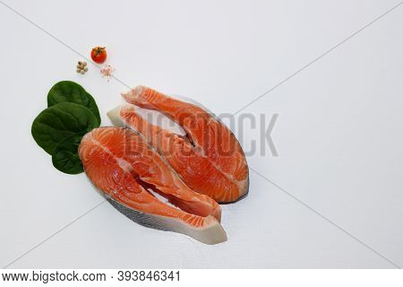 Two Large And Fatty Salmon Steaks On A White Background. Salmon, Salt, Pepper, Tomatoes And Spinach.