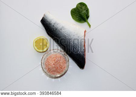 Fatty Salmon Carcass, Pink Salt, Spinach And Lemon On A White Plate. Salting Salmon At Home.