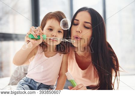Young Mother With Her Daughter Blowing Bubbles Together In Bedroom.