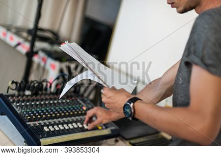 Behind The Scene. Sound Technician Adjusting Sound Elements For The Theatrical Performance And Looki