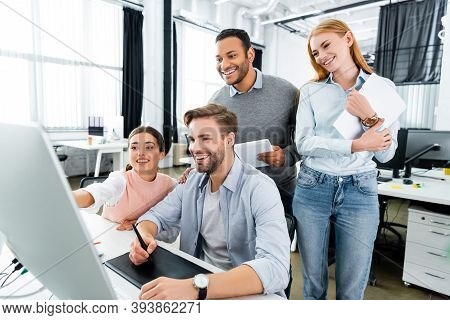 Multiethnic Businesspeople Standing Near Colleague Using Computer And Graphics Tablet In Office