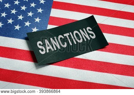 Usa Flag And Word Sanctions On The Black Piece Of Paper.