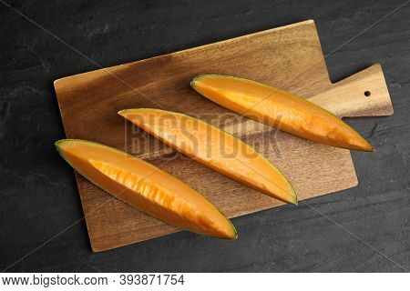 Slices Of Tasty Fresh Melon On Black Slate Table, Top View