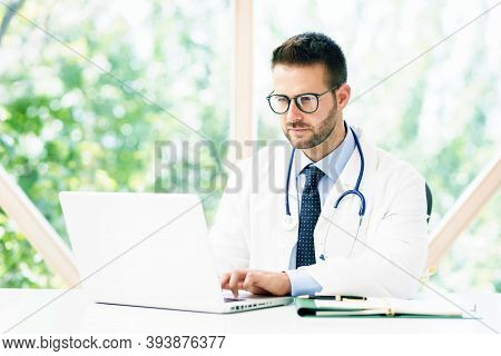 Portrait Shot Of Male Doctor Working On Notebook While Sitting At Desk In Doctor's Office.