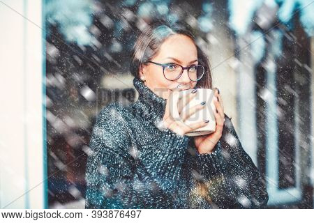 Close-up Portrait Shot Of Smiling Young Woman Holding A Cup Of Tea In Her Hand And Daydreaming While