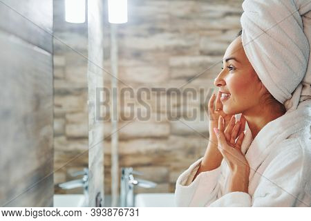Beautiful Young Woman In White Towel Standing In Bathroom And Taking Care Of Her Face.