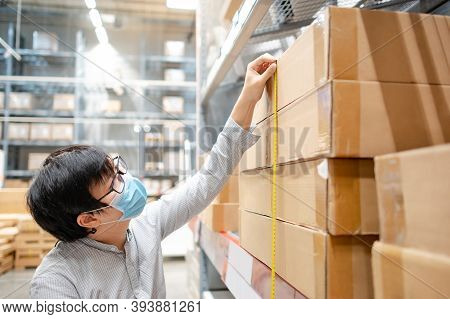 Asian Man Worker Wearing Face Mask Using Tape Measure For Measuring Dimension Of Product In Cardboar