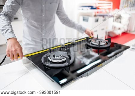 Male Hand Interior Designer Using Tape Measure On Gas Stove On Modern Countertop In Kitchen Showroom
