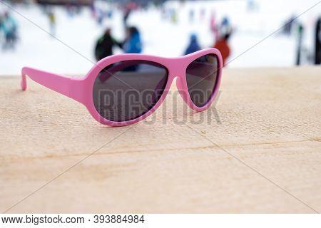 Pink-rimmed Sunglasses On Wooden Slope In Apres Ski Bar Or Cafe, With Ski Slope In Background, Copy
