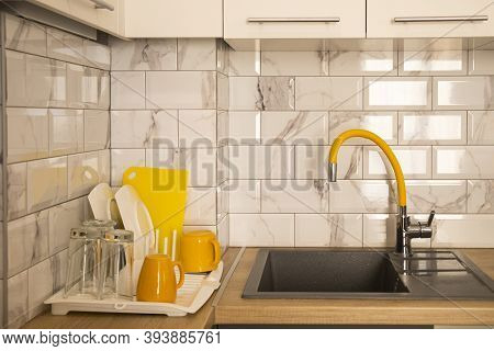 Modern Kitchen Interior With White Tile And Facades And Yellow Faucet And Dishes