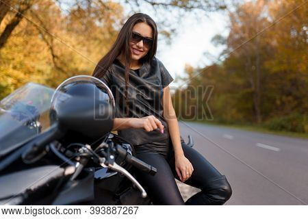 Beautiful Female Motorcyclist In Glasses And Black Leather Clothes Sits On Sport Bike