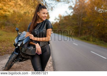 Female Motorcyclist Stands Near Motorcycle On Roadside And Holding Helmet