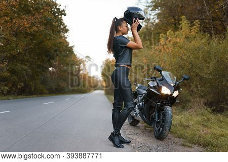 Young Female Motorcyclist Puts A Helmet On Her Head