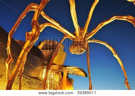 BILBAO, SPAIN - NOVEMBER 14: Guggenheim Museum and Maman sculpture on November 14, 2012 in Bilbao, Spain. The museum was designed by Frank Ghery and the sculpture, a giant spider, by Louise Bourgeois