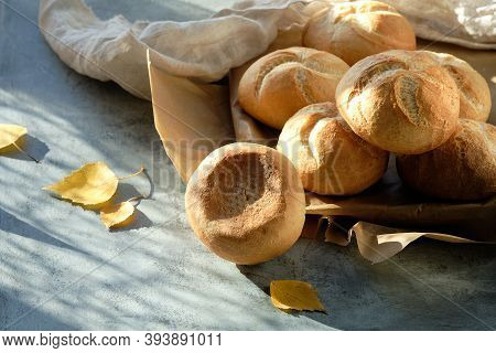 Kaiser, Or Vienna Buns In Bread Basket On Dark Background With Yellow Autumn Leaves.