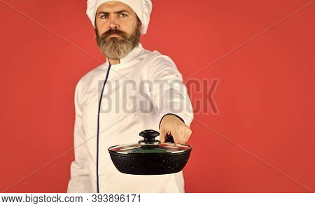 Bearded Cook In Uniform With Tools. Bearded Man Hold Cooking Pan. Preparing Food In Kitchen. Husband
