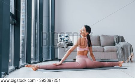 Does Exercises On Mat On The Floor. Young Woman With Slim Body Shape In Sportswear Have Fitness Day