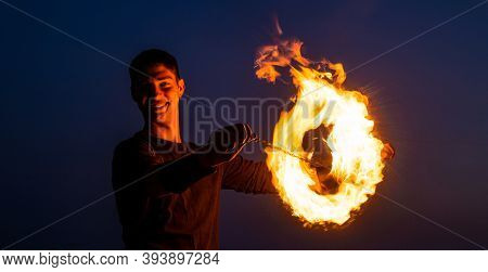 Happy Guy Artist Perform Fire Ring By Spinning Burning Poi On Idyllic Dark Sky At Night Outdoors, Ci