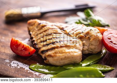 Grilled Chicken Breast With Sweet Peas On Butcher Board.