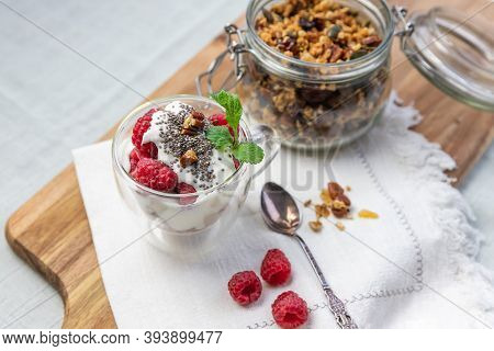 Granola In A Jar And In A Cup With Yogurt And Raspberry Top View. Granola Is A Breakfast Food And Sn