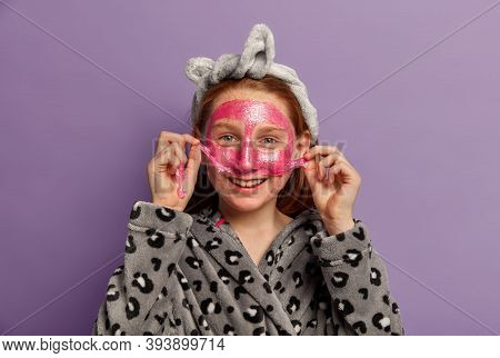 Indoor Shot Of Happy Female Child Takes Off Facial Mask, Cares About Complexion, Has Postive Smile,