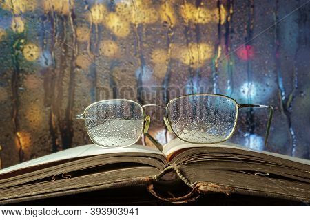 Glasses And Open Book On The Window Sill With Night Illuminated Background, Selective Focus