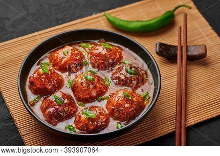 Veg Manchurian Gravy Balls In Black Bowl In Dark Slate Table Top. Vegetarian Manchurian Is Indian Ch