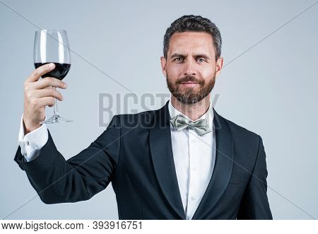 Handsome Tuxedo Man In Bow Tie Cheers With Glass Of Red Wine, Anniversary