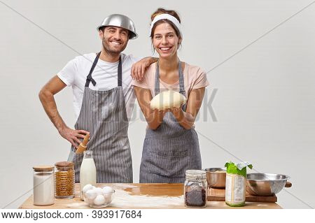 Indoor Shot Of Positive Friendly Hard Working Woman And Man Chefs Or Cooks Prepared Fresh Dough For