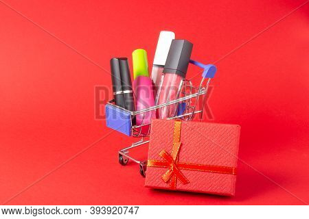 A Set Of Lipstick Cosmetics And Lip Glosses, Powder, Eyeshadow And A Shopping Trolley On A Bright Re