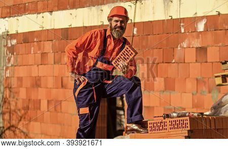 Happy Bearded Man Hold Brick. Brickwork. Man Takes Brick From The Pile. Male Construction Worker Hol