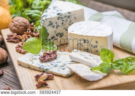 Fourme D'ambert Blue Cheese  And Walnuts. Wooden Background. Top View. Segment Of Blue Cheese Or Cam