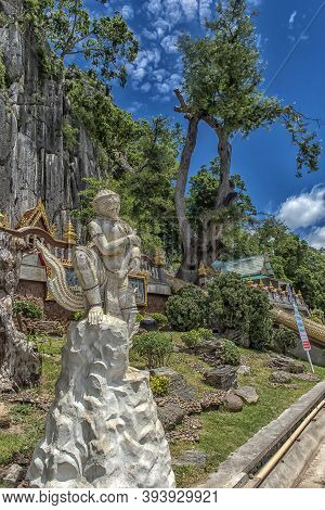 View Of Wat Tham Khao Yoi Cave, Buddhist Temple With Green Tree And Rock Mountain Background, In Phe
